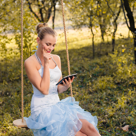totter: Beautiful young woman in prom dress sitting on swings and typing on tablet pc on green summer or autumn outdoors copyspace background