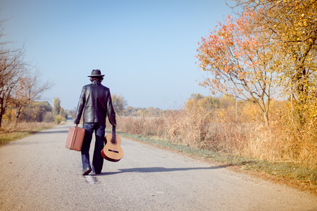 Young man musician in retro hat and leather jacket with vintage suitcase and guitar walking away on empty autumn road copy space background