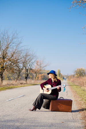 country music: Young retro woman musician in retro hat sitting on vintage suitcase and playing guitar on empty autumn road copy space background