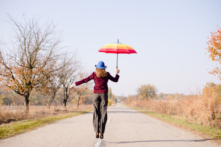 Young woman in blue retro hat, with colorful umbrella jumping high on empty autumn road copy space background photo