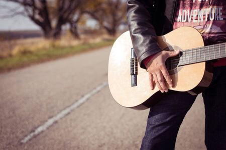 bard: Closeup image of male hand on guitar strings on autumn highway copyspace background Stock Photo