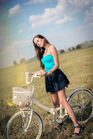 mini bike: beautiful cycling adventure: sexy young pretty lady having fun with bicycle in fields under bright blue summer sky on green copy space background, portrait