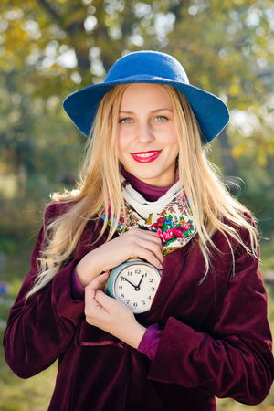 portrait of elegant beautiful blond young hipster woman having fun holding retro alarm clock on sunny autumn outdoors copy space background photo