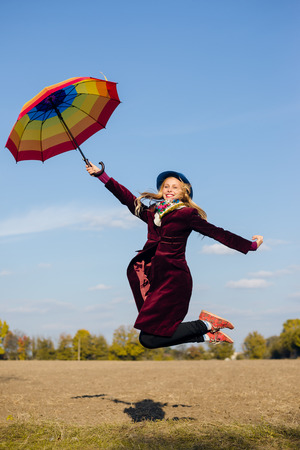 Young happy woman with colorful umbrella jumping high on empty autumn field copy space background photo