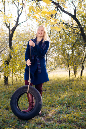portrait of elegant beautiful blond young woman having fun on tire swing happy smiling and looking at camera on autumn copy space outdoors background photo