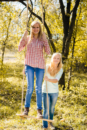 Two happy teenage girls sitting on swing together in autumn park or garden background on bright sunny day photo