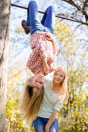 beautiful preteen girl: Two teenage girls having fun in park hanging upside down on green countryside rural copy space background