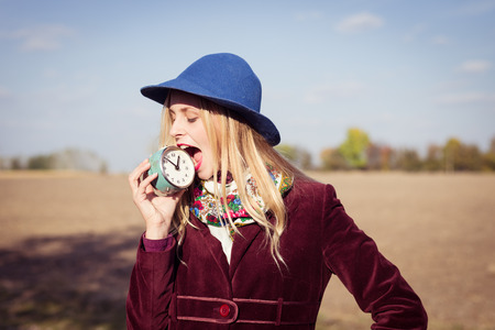 portrait of elegant beautiful blond young hipster woman having fun holding retro alarm clock trying to bite it on sunny autumn outdoors copy space background photo
