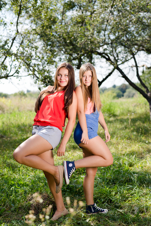 portrait of 2 pretty girlfriends having fun relaxing happy smiling with excellent white teeth & looking at camera on green park or garden outdoors copy space background photo