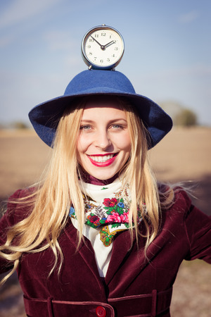 portrait of elegant beautiful blond young hipster woman having fun holding retro alarm clock on top of blue hat on sunny autumn outdoors copy space background photo