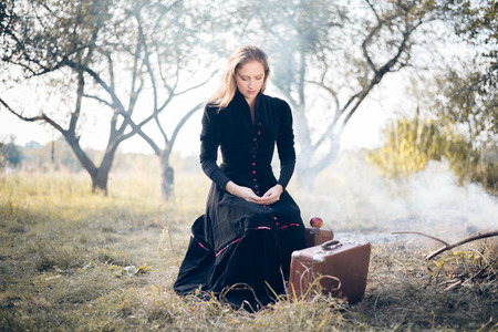 Young lady in retro overcoat with vintage suitcase waiting in autumn park with burning leaves and smoke copyspace background