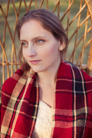 Contemplating young woman wrapped in red shepherd plaid portrait photo