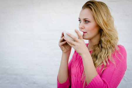 Happy young blond woman drinking hot tea or coffee and looking joyful over pin brick wall photo