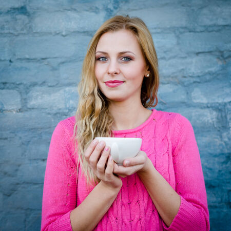 Happy young blond woman enjoying hot tea or coffee and smiling over blue brick wall photo