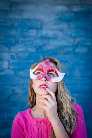 Happy young blond woman wearing carnival mask and smiling over blue brick wall with sun flare copy space background