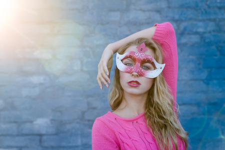 Happy young blond woman wearing carnival mask and smiling over blue brick wall with sun flare copy space background photo