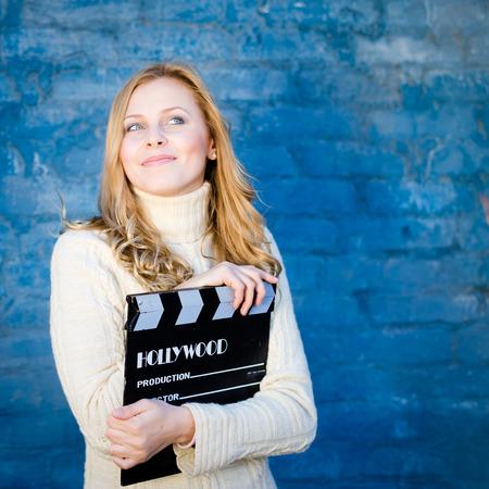 casting: Gl�ckliche junge blonde Frau im wei�en gestrickten Pullover mit Kinofilmklappe l�chelnd �ber blauen Beton oder Ziegelwand Kopie Raum Hintergrund