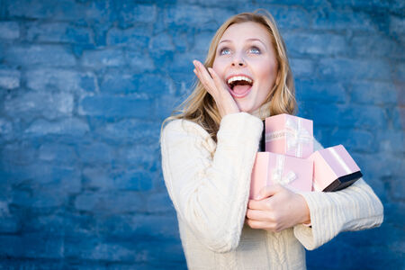 obtain: attractive blond young woman in woolen sweater receiving presents having fun happy smiling on blue brick wall background
