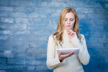 image of beautiful blond young lady in white wool sweater using tablet pc at blue concrete wall copy space background photo