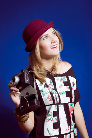 Studio portrait of teenage hipster girl with retro photo camera wearing trendy hat over blue copy space background photo