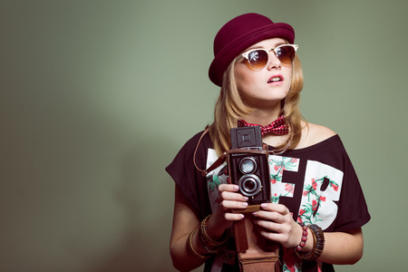 Studio portrait of teenage hipster girl wearing trendy hat and sunglasses with retro photo camera over olive copy space background photo