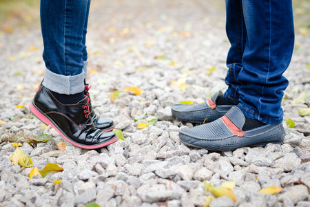 Teenage couple feet closeup in black leather shoes when reaching for kiss photo