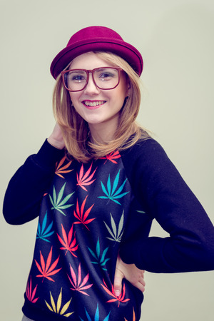 rasta hat: Studio portrait of teenage hipster girl wearing trendy eyeglasses and hat over olive copy space background Stock Photo