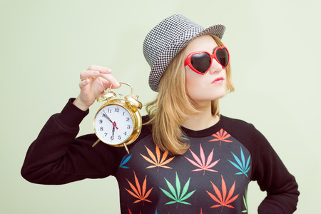 rasta hat: Studio portrait of teenage hipster girl wearing trendy eyeglasses and hat with alarm clock over olive copy space background