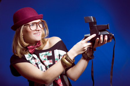 Studio portrait of teenage hipster girl wearing trendy hat and super size eyeglasses with making selfie retro photo camera over blue copy space background photo
