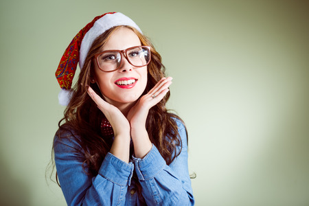 Funny hipster girl in super size eyeglasses wearing xmas santa hat over olive copy space background photo