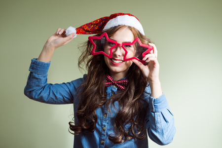 happy smiling and exciting looking at camera funny hipster beautiful young lady in super size star shape glasses wearing xmas santa hat over olive copy space background photo