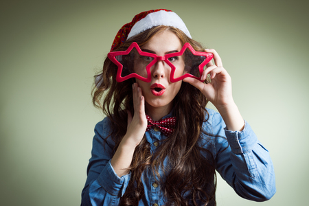 exciting looking at camera funny hipster beautiful young lady in super size star shape glasses wearing xmas santa hat over olive copy space background photo