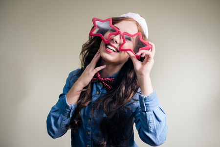 Funny hipster girl in super size star shape glasses wearing xmas santa hat over olive copy space background photo