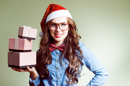 Funny hipster girl in super size eyeglasses wearing xmas santa hat holding three boxes of presents over olive copy space background photo