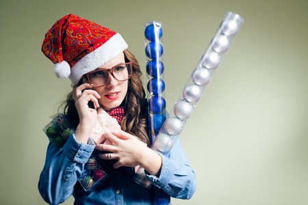 picture of making phone call & holding present box funny hipster girl in sunglasses wearing xmas santa hat over olive copy space background photo