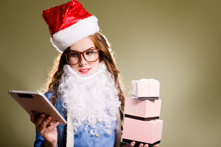 Funny hipster girl in super size eyeglasses wearing xmas santa hat and faux beard holding three boxes of presents and tablet pc over olive copy space background photo