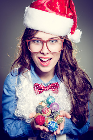closeup portrait of holding present box funny hipster girl in sunglasses wearing Christmas Santa hat over olive copy space background, happy smiling and looking at camera photo