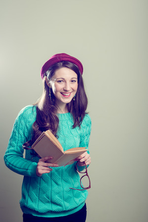 Studio portrait of holding a book & big glasses hipster or hippie pretty girl having fun wearing knitting sweater happy smiling and looking at camera over copy space background photo