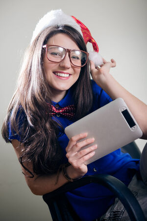 Funny hipster pretty girl in super size eyeglasses wearing xmas santa hat holding tablet pc computer over olive copy space background photo