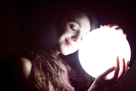 closeup image of beautiful young sleeping woman holding ball of light and happy smiling photo