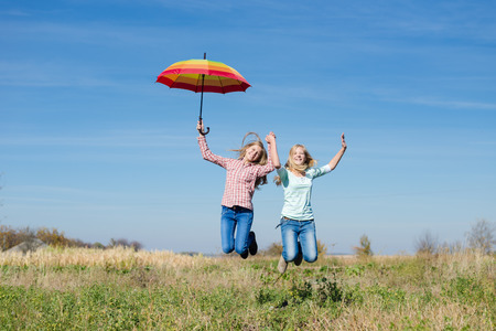 Two young happy teenage girls with colorful umbrella jumping high on empty autumn field copy space background photo