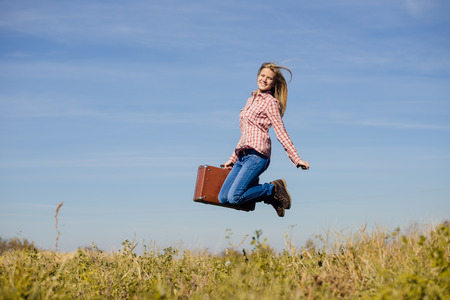 Funny happy teenage girl jumping with retro suitcase over blue sky copy space background photo