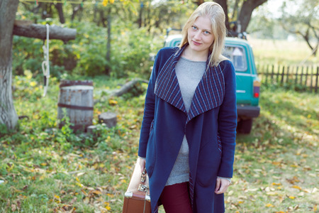 portrait of young lady in retro overcoat with vintage suitcase waiting in autumn park copy space background photo