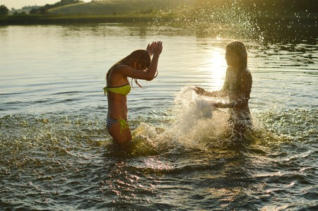 young teen girl nude: 2 sisters girlfriends having fun playing together in the lake at sunset Stock Photo