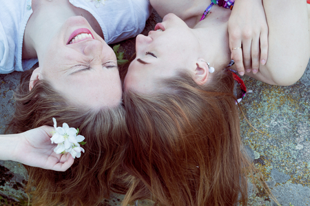 closeup portrait of lying head to head happy girl friends relaxing happy smiling photo