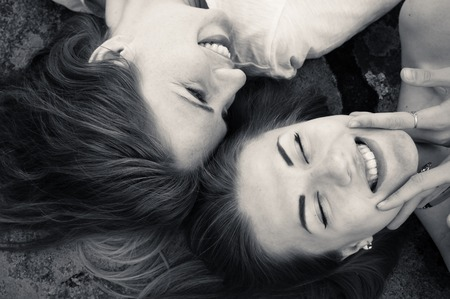 closeup picture of happy girl friends relaxing head to head happy smiling photo