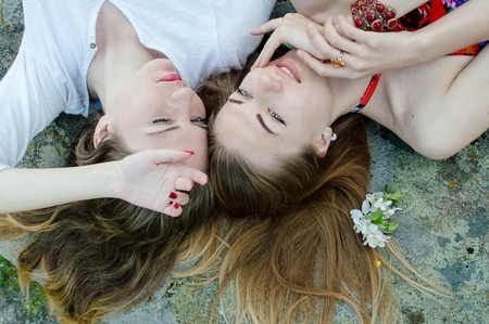 Closeup portrait of calm pretty young ladies friends relaxing on stone abstract background photo