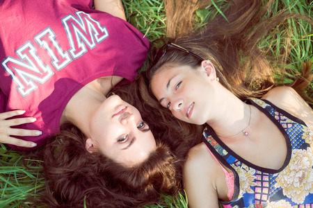 jungle girl: Beautiful young girls having fun lying on grass happy smile on green outdoors background Stock Photo