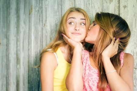 sex education: Portrait of two pretty girlfriends kissing