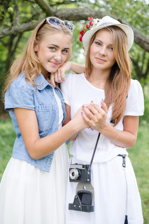 portrait of hugging 2 beautiful young women having fun taking photo on green outdoors background photo